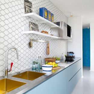 Design ideas for a mid-sized contemporary single-wall open plan kitchen in Lyon with a double-bowl sink, flat-panel cabinets, blue cabinets, stainless steel benchtops, multi-coloured splashback and no island.