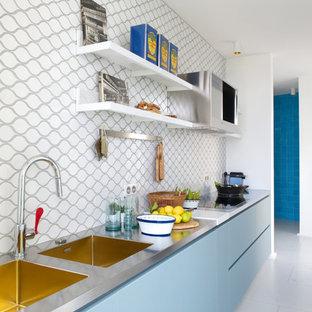 Aménagement d'une cuisine ouverte linéaire contemporaine de taille moyenne avec un évier 2 bacs, un placard à porte plane, des portes de placard bleues, un plan de travail en inox, une crédence multicolore et aucun îlot.