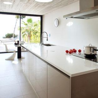 Idée de décoration pour une cuisine américaine linéaire design de taille moyenne avec un évier encastré, un placard à porte plane, des portes de placard grises et un îlot central.