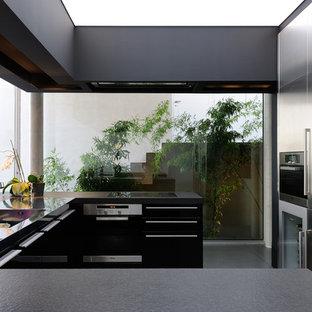 Cette image montre une cuisine ouverte design en U de taille moyenne avec un évier intégré, un placard à porte plane, une façade en inox, un électroménager en acier inoxydable et aucun îlot.