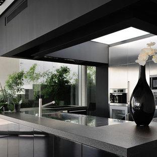 Exemple d'une cuisine ouverte parallèle tendance de taille moyenne avec un évier intégré, une façade en inox, un électroménager en acier inoxydable et un îlot central.