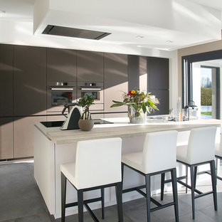 Aménagement d'une grande cuisine contemporaine avec un placard à porte plane, des portes de placard marrons, un électroménager de couleur, un îlot central et un plan de travail en bois.