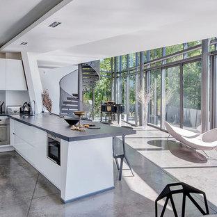 Aménagement d'une cuisine ouverte contemporaine avec un évier 1 bac, un placard à porte plane, des portes de placard blanches, une crédence blanche, un électroménager en acier inoxydable, béton au sol, une péninsule et un sol gris.