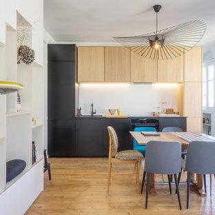 Cette photo montre une petit cuisine américaine linéaire rétro avec un évier encastré, une crédence blanche, un électroménager encastrable, un placard à porte plane, des portes de placard noires, un sol en bois brun, aucun îlot et un sol marron.