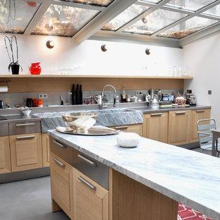 Idée de décoration pour une grand cuisine américaine design en L avec un évier de ferme, un placard avec porte à panneau surélevé, des portes de placard en bois clair et un îlot central.