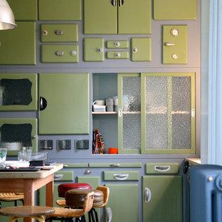 Cette image montre une cuisine linéaire bohème fermée et de taille moyenne avec des portes de placards vertess et un îlot central.