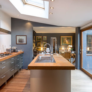 This is an example of a large contemporary galley open plan kitchen in Rennes with an undermount sink, stainless steel cabinets, wood benchtops, medium hardwood floors and with island.