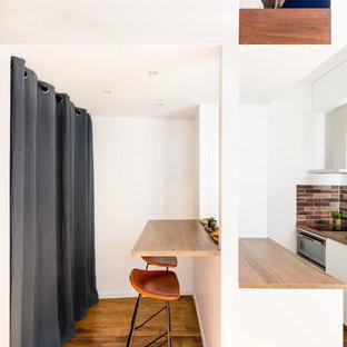 Idées déco pour une petite cuisine américaine parallèle industrielle avec un placard à porte plane, des portes de placard blanches, un plan de travail en bois, une crédence marron, un électroménager en acier inoxydable, un sol en bois brun, un sol marron, un plan de travail marron, un évier 1 bac, une crédence en carrelage de pierre et un îlot central.