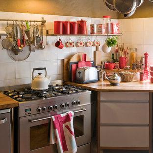 Aménagement d'une cuisine campagne en L fermée et de taille moyenne avec un placard à porte plane, des portes de placard blanches, un électroménager en acier inoxydable et aucun îlot.