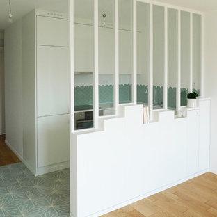 パリの小さいコンテンポラリースタイルのおしゃれなキッチン (アンダーカウンターシンク、フラットパネル扉のキャビネット、白いキャビネット、珪岩カウンター、緑のキッチンパネル、セラミックタイルのキッチンパネル、パネルと同色の調理設備、セメントタイルの床、アイランドなし、ターコイズの床、白いキッチンカウンター) の写真
