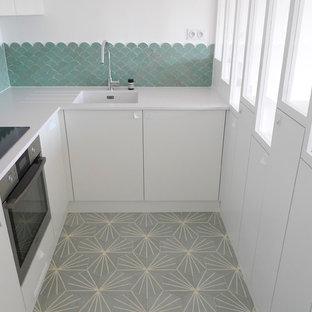 Inredning av ett modernt litet vit vitt kök, med en undermonterad diskho, släta luckor, vita skåp, bänkskiva i kvartsit, grönt stänkskydd, stänkskydd i keramik, integrerade vitvaror, cementgolv och turkost golv