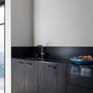 Diseño de cocina en L, actual, de tamaño medio, cerrada, sin isla, con fregadero integrado, puertas de armario negras, encimera de madera, salpicadero negro, salpicadero de madera, electrodomésticos con paneles, suelo de terrazo y encimeras negras