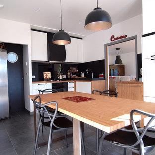 Cette image montre une cuisine minimaliste en L fermée et de taille moyenne avec un évier 2 bacs, un placard à porte affleurante, des portes de placard blanches, un plan de travail en bois, une crédence noire, une crédence en ardoise, un électroménager noir, un sol en carrelage de céramique, aucun îlot et un sol gris.