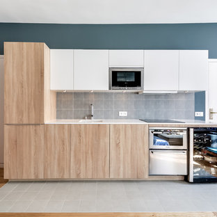 Inspiration for a mid-sized scandinavian single-wall open plan kitchen in Paris with an undermount sink, light wood cabinets, blue splashback, ceramic splashback, stainless steel appliances, ceramic floors and no island.