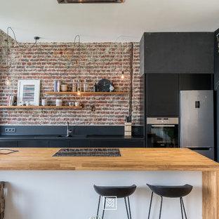 リヨンの小さいインダストリアルスタイルのおしゃれなキッチン (ドロップインシンク、フラットパネル扉のキャビネット、黒いキャビネット、木材カウンター、赤いキッチンパネル、レンガのキッチンパネル、シルバーの調理設備、無垢フローリング、茶色い床) の写真