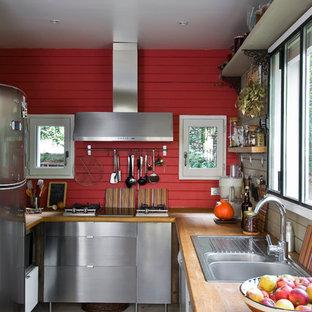 Réalisation d'une cuisine champêtre en U fermée et de taille moyenne avec un placard à porte plane, une façade en inox, un plan de travail en bois, aucun îlot, un évier 2 bacs, un électroménager en acier inoxydable et un sol en bois clair.