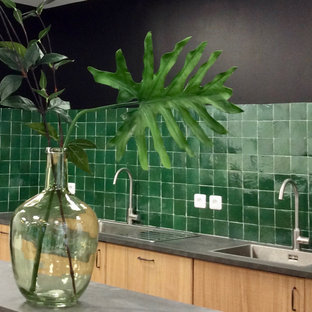 This is an example of a tropical kitchen in Paris with an undermount sink, flat-panel cabinets, light wood cabinets, laminate benchtops, green splashback, panelled appliances, ceramic floors and grey benchtop.
