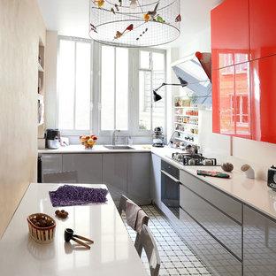 Cette image montre une cuisine américaine design en L de taille moyenne avec un évier encastré, un placard à porte plane, des portes de placard grises et aucun îlot.