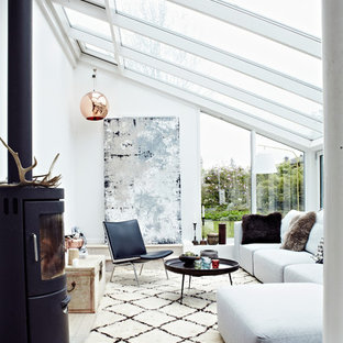 Diseño de salón nórdico, sin televisor, con paredes blancas, suelo de madera clara y estufa de leña