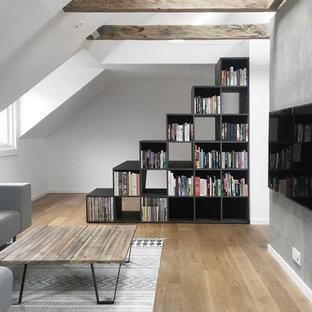 Foto de salón abierto, escandinavo, con paredes grises, suelo de madera en tonos medios y televisor colgado en la pared