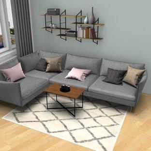 Modelo de salón para visitas cerrado, minimalista, de tamaño medio, con paredes verdes, suelo de madera clara y televisor colgado en la pared