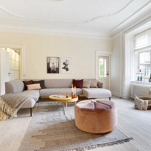 Foto de salón cerrado, nórdico, grande, sin chimenea, con suelo de madera clara, paredes beige y suelo beige