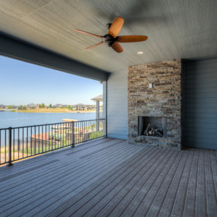 Inspiration for a modern deck remodel in Omaha with a fireplace and a roof extension
