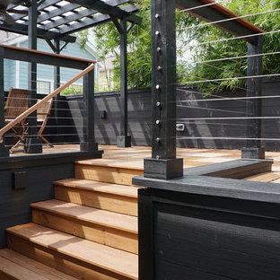 Bild på en mellanstor funkis terrass på baksidan av huset, med takförlängning