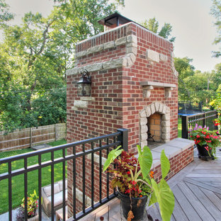 Example of a large transitional backyard deck design in St Louis with a fire pit and no cover