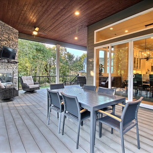Example of a huge arts and crafts backyard deck design in Portland with a fire pit and a roof extension