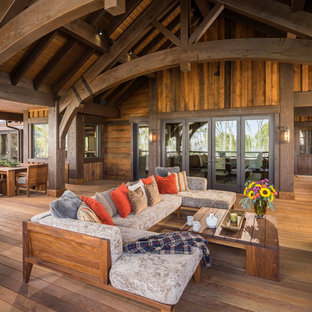 Inspiration for a large rustic backyard deck remodel in Salt Lake City with a fire pit and a roof extension