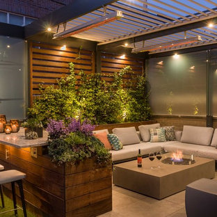 This is an example of a contemporary rooftop deck in Chicago with a fire feature and a pergola.