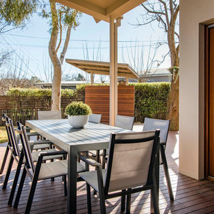 Photo of a contemporary backyard deck in Canberra - Queanbeyan with a pergola.