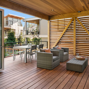 Inspiration for a contemporary backyard deck remodel in Seattle with a roof extension
