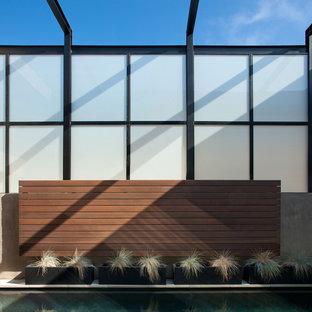 Idee per una terrazza minimalista di medie dimensioni e nel cortile laterale con fontane e un tetto a sbalzo