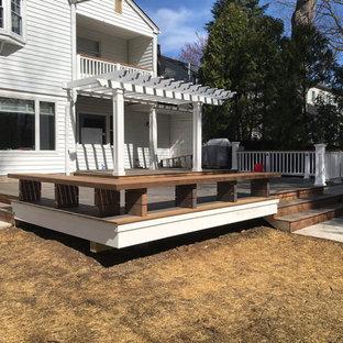 Foto di un'ampia terrazza tradizionale dietro casa con un pontile e una pergola
