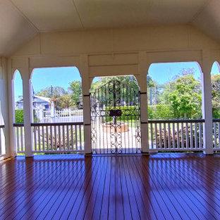 Exemple d'une grande terrasse latérale chic avec des solutions pour vis-à-vis et une extension de toiture.