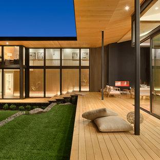 Idéer för att renovera en mycket stor funkis terrass på baksidan av huset, med takförlängning