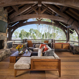 Inspiration for a rustic deck remodel in Other with a fireplace and a roof extension