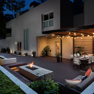 Photo of a large contemporary backyard deck in Atlanta with a fire feature and a pergola.