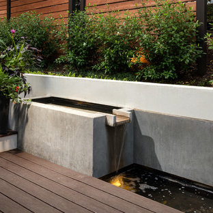 Example of a large trendy backyard water fountain deck design in Atlanta with a pergola