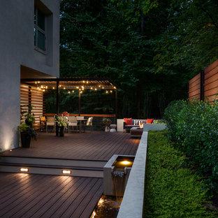 Foto di una grande terrazza design dietro casa con un focolare e una pergola