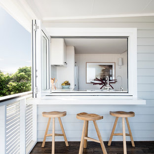 Inspiration for a beach style backyard deck in Sydney with a roof extension.