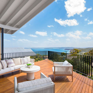 Photo of a mid-sized beach style deck in Sydney with with dock and a roof extension.