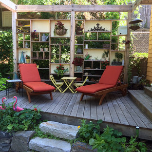 Inspiration for a small eclectic backyard deck container garden remodel in Boston with a pergola