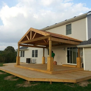 Huge arts and crafts backyard deck photo in Indianapolis with a roof extension