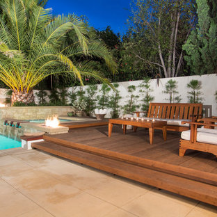 Example of a mid-sized island style backyard deck design in Orange County with no cover
