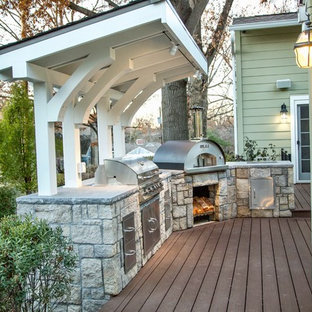 Outdoor kitchen deck - mid-sized traditional backyard outdoor kitchen deck idea in Kansas City with a pergola
