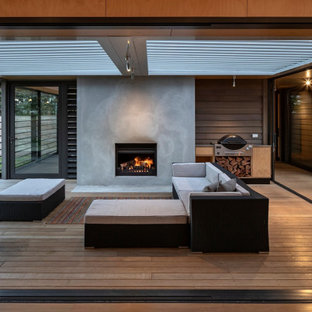 Mid-sized beach style courtyard deck photo in Other with a fireplace and a pergola