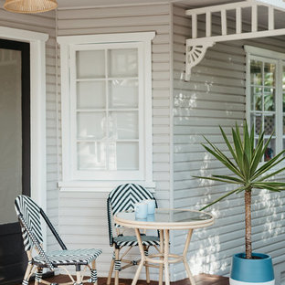 Design ideas for a beach style backyard deck in Sydney with a roof extension.